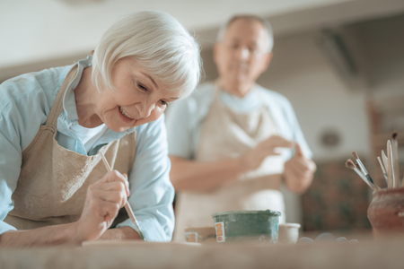 Cropped photo of elderly craftswoman painting decorative plate in workshop