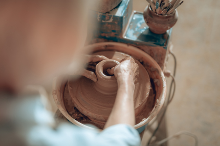 Cropped photo of female hands shaping jug at workshop