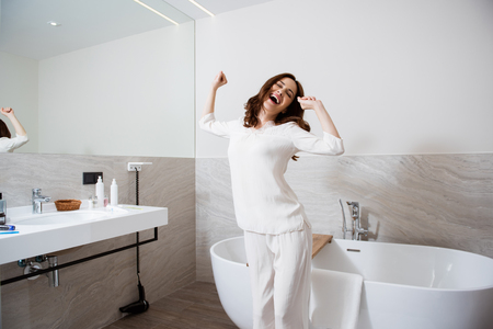 Cheerful woman stretching herself in the bathroom 免版税图像
