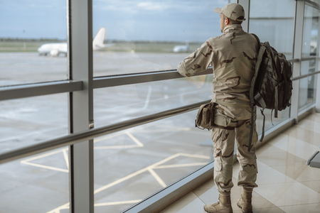 Full length of American soldier in camouflage looking at the window Standard-Bild - 124525962