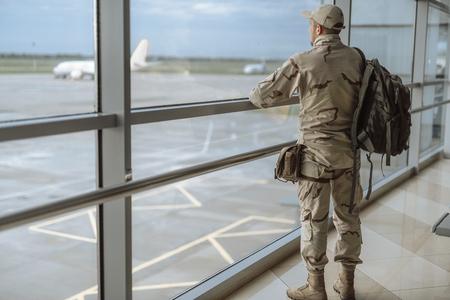 Toute la longueur du soldat américain en tenue de camouflage regardant la fenêtre Banque d'images