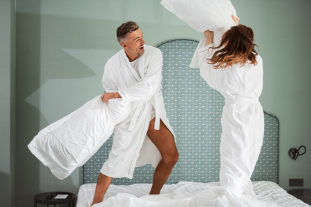 Excited young couple having pillow fight and smiling