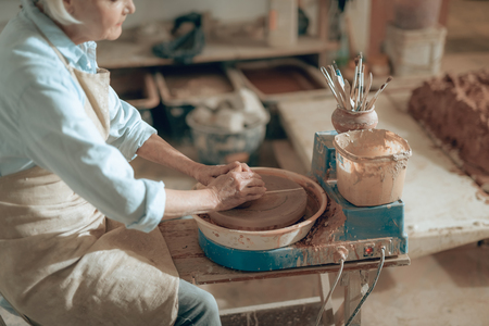 High angle of old clay master working with clay in potters studio Stockfoto