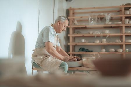Side view of craftsman working on potters wheel in his workshop Stock fotó - 124524856