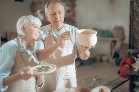 Half length of happy mature potters working in potters studio