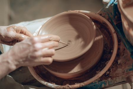 Cropped photo of male arms with stick over ceramic bowl