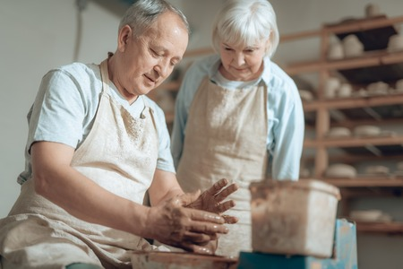 Cropped photo of senior couple in aprons working in potters studio