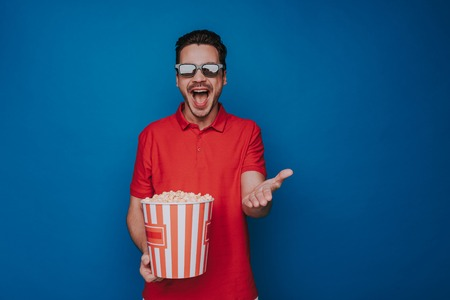 Waist up of Caucasian emotional man holding popcorn bucket on blue background Фото со стока