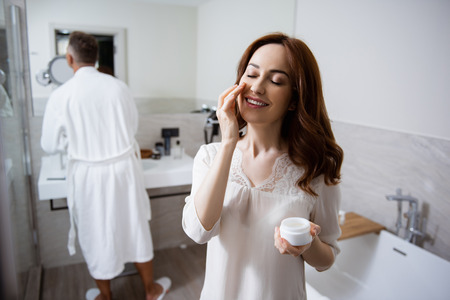 Happy woman closing her eyes while using her new face cream Stock Photo - 124908289
