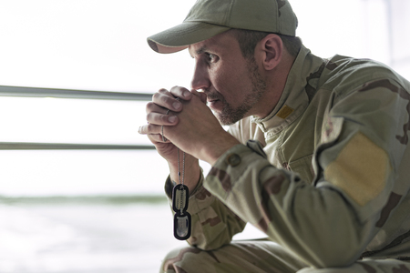 Low angle of American soldier in camouflage praying indoors