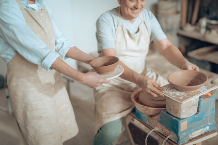 High angle of two potters showing their works in potters studio