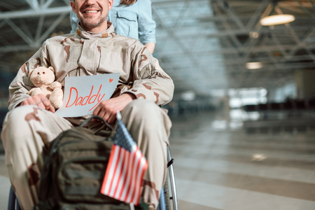 Woman carrying wheelchair and situating behind her husband in military uniform Stock Photo
