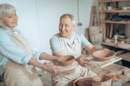 High angle of two clay masters showing their works in potters studio