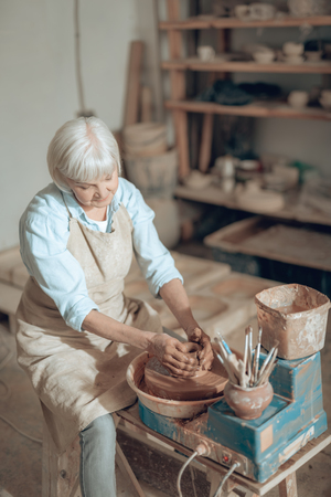 Cropped photo of elderly craftswoman making earthenware in potters studio