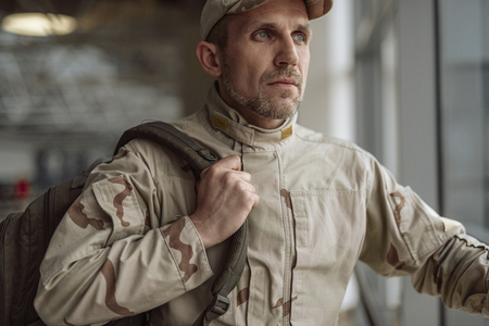 Waist up of serious American soldier in camouflage looking away