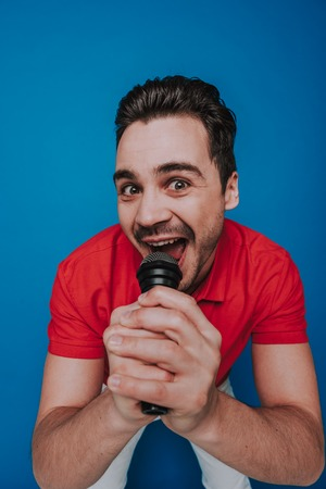 Portrait of unshaven cheerful guy looking at camera with microphone in arm Reklamní fotografie