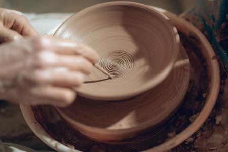 Primo piano di braccia maschili con bastone su piatto in ceramica Archivio Fotografico