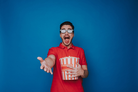 Waist up of Caucasian emotional man holding popcorn bucket on blue background Фото со стока - 124628186