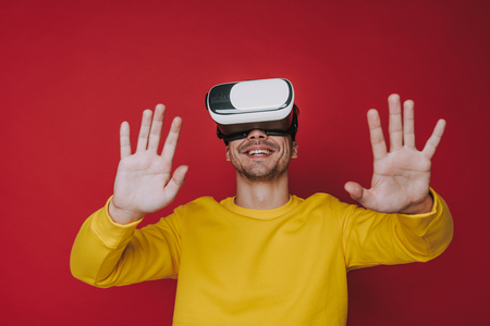 Low angle of smiling man touching something while situating in virtual reality Фото со стока - 124628189