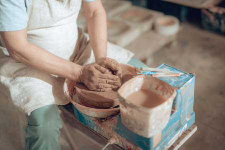Cropped photo of male hands working with wet clay in potters studio 版權商用圖片