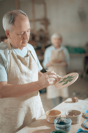 Waist up of elderly craftsman working in potters studio Stockfoto