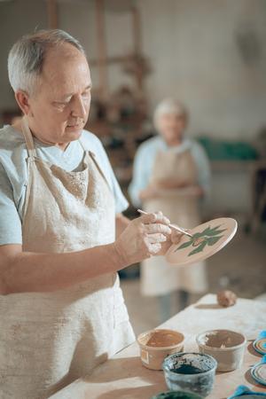 Waist up of elderly craftsman working in potters studio Imagens