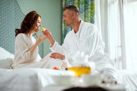 Smiling man feeding young woman with tasty dessert Stock Photo