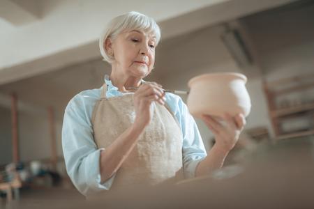 Ángulo bajo de vieja artesana pintando su bote en el taller
