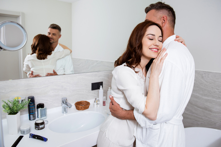 Waist up of a loving couple hugging in the bathroom and smiling