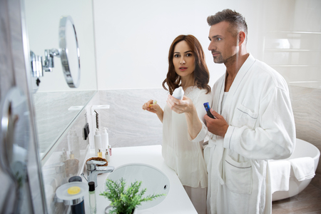 Woman pointing to the camera with toothpaste while standing with husband