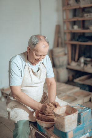 Waist up of elderly craftsman making earthenware in potters studio