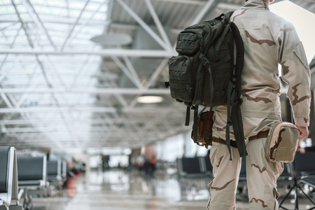 Cropped photo of American soldier in camouflage carrying backpack Stockfoto