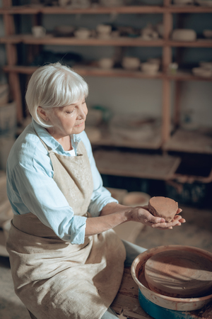 High angle of mature craftswoman making clay products in potters studio 写真素材 - 124534677