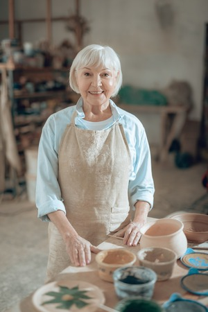 Waist up of smiling old craftswoman looking at camera in workshop Stock fotó - 124532837