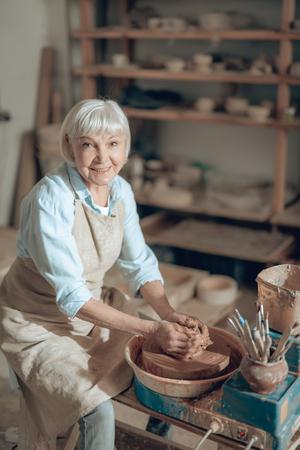 Photo recadrée d'une artisane mature faisant un bol dans un studio de potiers