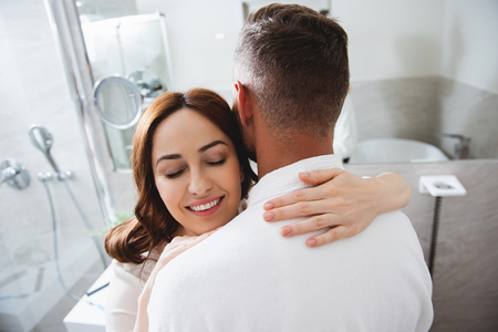 Man in bathrobe and contented lady hugging him Stock Photo
