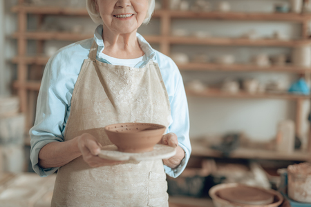 Elderly happy female potter is showing her work in potters studio Stockfoto