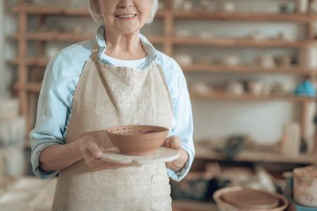 Une potière heureuse âgée montre son travail dans un studio de potiers
