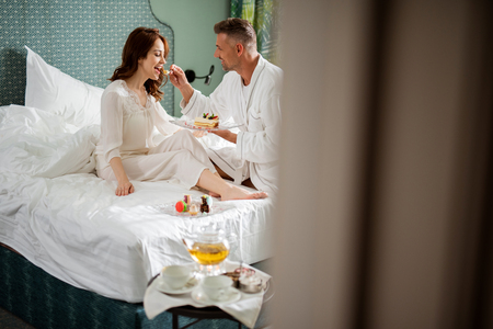 Happy woman on the bed and man giving cake to her