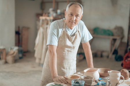 Waist up of handsome mature craftsman looking at camera in workshop Stock fotó - 124533085