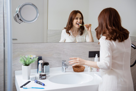 Happy woman taking care of her teeth and brushing them