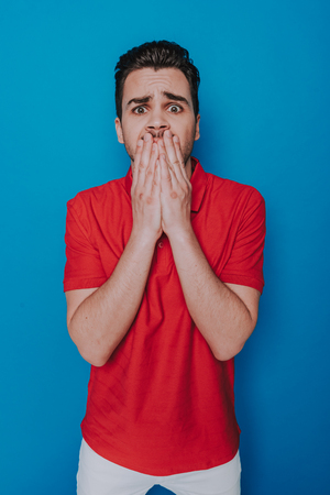 Portrait of a shocked young man covering his mouth with hands Reklamní fotografie