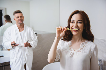 Confident woman looking happy while brushing teeth