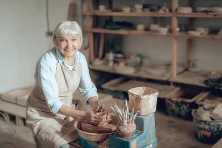 Waist up of elderly craftswoman making ceramic bowl in potters studio