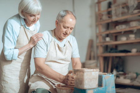 Senior couple enjoying of work with wet clay in pottery workshop