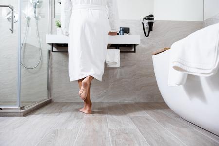 Person im weißen Bademantel steht vor dem Waschbecken