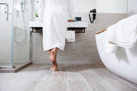 Person in white bathrobe standing in front of the sink Stok Fotoğraf