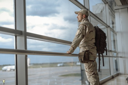Side view of American soldier in camouflage looking at window Archivio Fotografico
