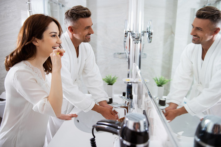 Happy man washing hands while his wife brushing her teeth