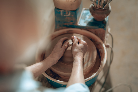 Cropped photo of female hands with clay in workshop Banco de Imagens